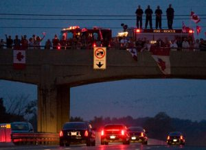 People line a bridge in Whitby, Ontario, Canada to pay respects to the passing convoy for the three deceased soldiers following their repatriation to Canada on Saturday, Aug. 23, 2008. A roadside blast Wednesday killed the three soldiers in the southern Afghanistan province of Kandahar, Canada's Department of National Defense said. Their deaths bring to 93 the number of Canadian soldiers who have died during the Afghan mission since it began in 2002. (AP Photo/The Canadian Press, Frank Gunn)