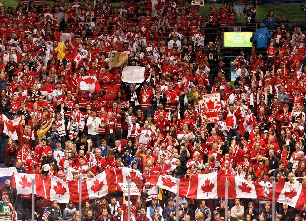 "Team Canada fans singing the ""Oh Canada"" at hockey game."